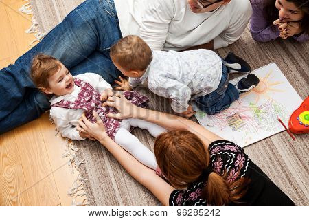 family group of five - two babies and three adults lying on the carpet, mom is tickling her daughter.