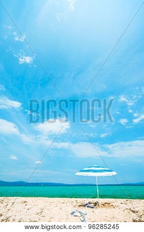 A single umbrella with two pairs of sandals and a scarf underlined on an empty beautiful sunny beach. Vertical composition.