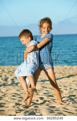 Two kids - seven and three on the beach playing. Sister is lifting and spinning around her younger brother laughing.