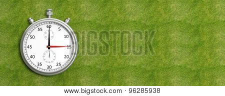 Silver chronometer on green grass