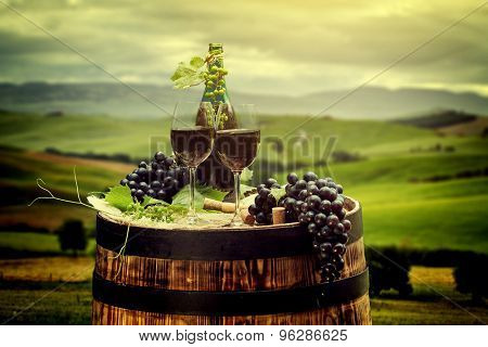 Red wine bottle and wine glass on old wood  barrel. Beautiful Tuscany background