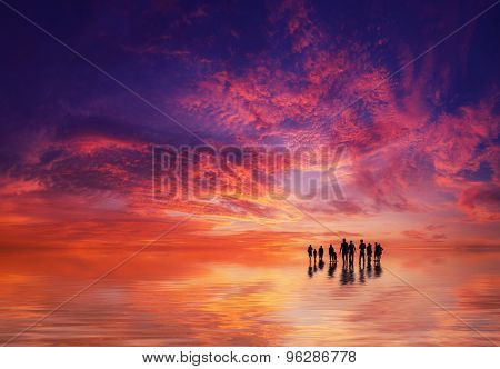 Silhouettes of people at sunset on the beach of Kuta Bali Indonesia