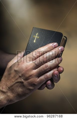 Man holding an old small black bible in his hands. Short depth of field, the sharpness is in the cross.