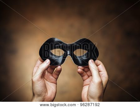 Man holding a black eye mask in his hands.
