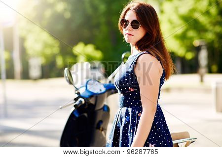 Young woman standing next to the scooter