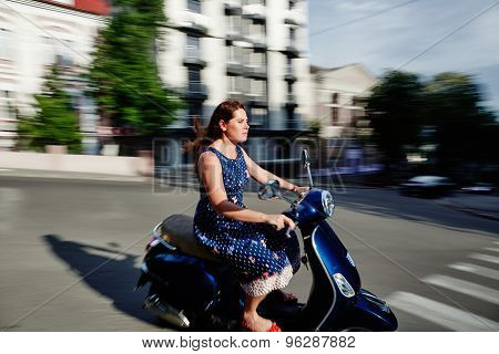 Young woman riding the scooter