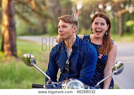 Young couple laughing while sitting on the scooter
