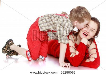Little boy kisses his young beautiful mother