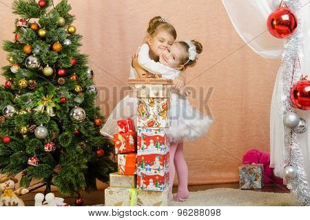 Two Little Girls Hugging Each Other In A Christmas Setting