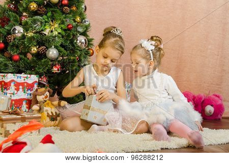 Two Girls Open A Box With Christmas Present