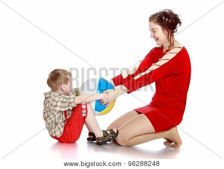 Mother and son playing with a ball sitting on the floor