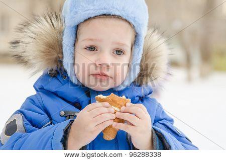 The Girl Eats A Bun In Street In Winter