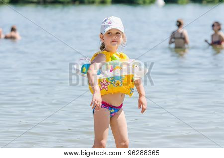 Four-year Girl On The Beach Wearing A Life Jacket And Circle