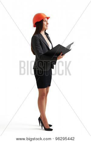 full length portrait of smiley businesswoman in orange hardhat holding black folder and looking up. isolated on white background