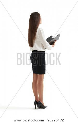full-length portrait of serious businesswoman in formal wear holding open folder and looking forward. isolated on white background