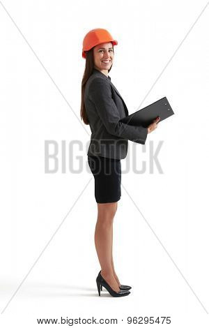 sideview full length portrait of smiley businesswoman in orange hardhat holding black folder and looking at camera. isolated on white background