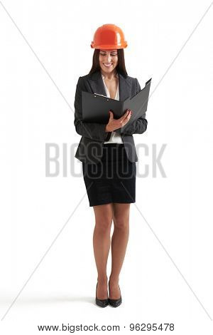 full length portrait of smiley businesswoman in orange hardhat holding black folder and reading documents. isolated on white background