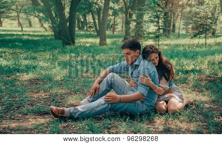 Loving Couple Sitting In Summer Park