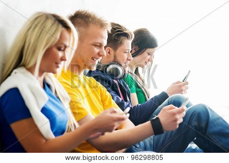 Group of students on a break. Focus on a boy using smartphone. Background is blurry.