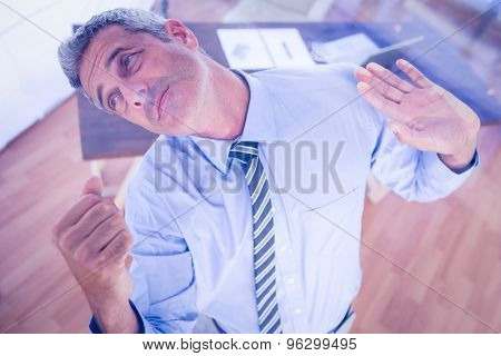 A serious businessman lifting something in office