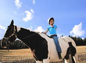 foto of horse riding  - beautiful smiling girl taking riding lessons on a paint pony
