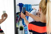 foto of antidepressant  - Blonde woman standing near wardrobe rack full of clothes and mirror making selfie with cellphone - JPG