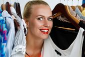picture of antidepressant  - Beautiful smiling blonde woman standing inside wardrobe rack full of clothes happy to have it - JPG