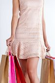 picture of antidepressant  - Beautiful walking legs of a woman in dress holding colored paper bags - JPG