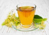 image of linden-tree  - Cup of herbal tea with linden flowers on a old wooden background - JPG