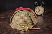 picture of sherlock  - Deerstalker or Sherlock Hat and magnifying glass on Old Wooden table - JPG