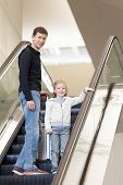 stock photo of escalator  - family of two with suitcase standing at the escalator at the airport ready for journey or family vacation - JPG