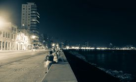 stock photo of malecon  - Along the Malecon Havana Cuba people out at night in warm sea air sitting on sea wall across from the colonial buildings with the more modern city lights in distance - JPG
