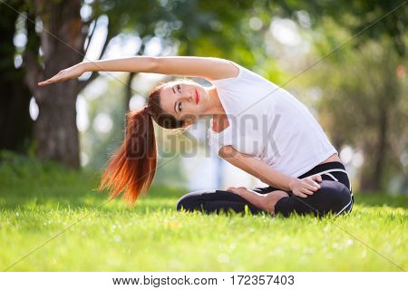 poster of Yoga outdoor. Happy woman doing yoga exercises, meditate in the park. Yoga meditation in nature. Con