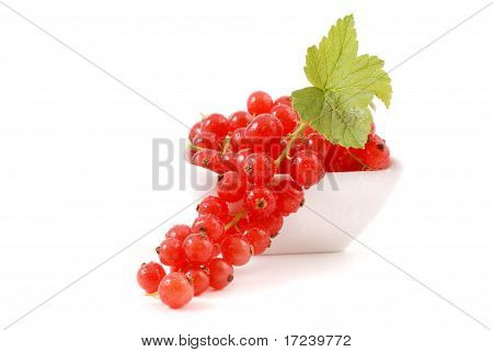 Bunch of red currants in cup on a white background