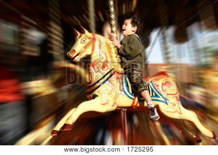 Young Boy Thrilled On The Carousel Ride, With Movement Effect.