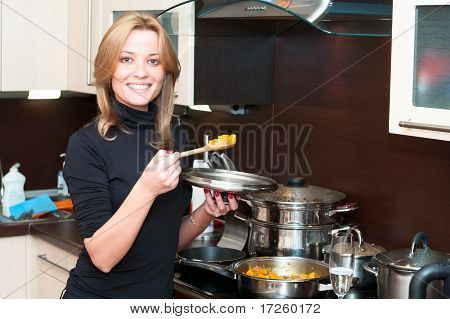 Beautiful happy smiling woman in kitchen interior with pan.