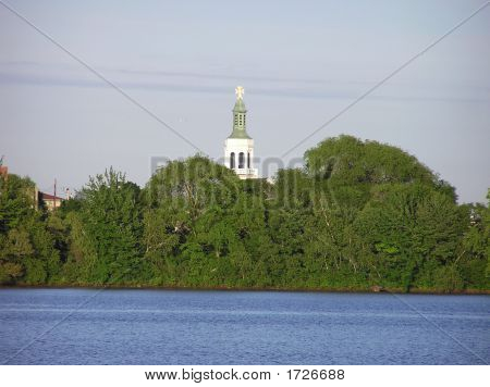 White Church Steeple Above Trees by a Lake