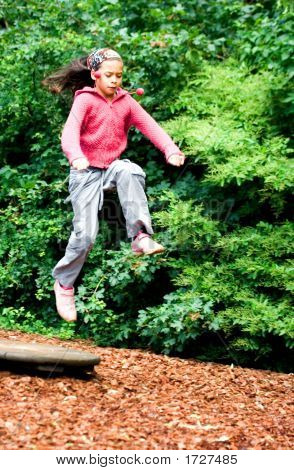 Girl Leaps Into The Air In The Park