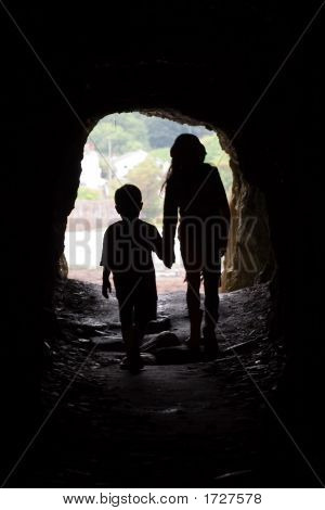 Silhouette Of Girl And Younger Brother At Cave Mouth