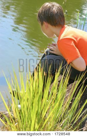 Boy Sitting By The Lake