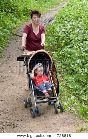 Mum And Child In A Walking Carriage