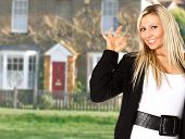 picture of real-estate agent  - A very happy estate agent promoting a house showing a gesture for perfection - JPG