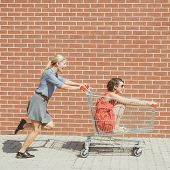 Friends having fun with shopping cart at a mall poster