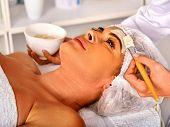 Facial mask and massage for forty five year old woman . Portrait of woman middle-aged take face clea poster