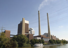 picture of coal barge  - power plant with a coal delivering barge on the canal in front of it - JPG