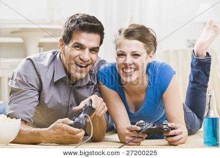 ein junges Paar spielen von Videospielen. Sie Lächeln und lachen, und sind auf dem Boden. h