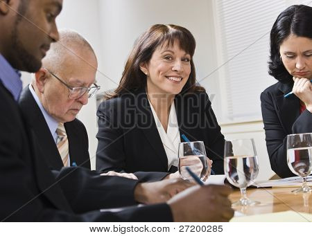 A group of business people are seated around a desk in a meeting.  They are looking away from the camera.  Horizontally framed shot.