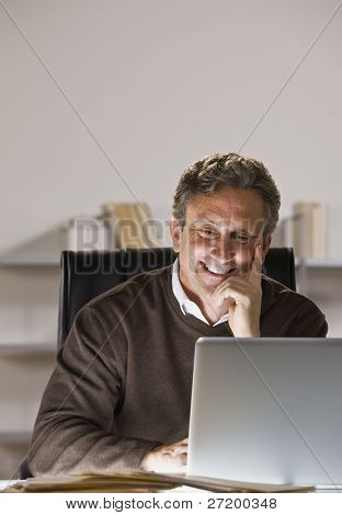 A man is seated at a desk and is working on a laptop.  He is smiling and looking at the screen.  Vertically framed shot.