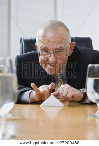 Playful senior male sitting at desk flicking paper football. Vertical