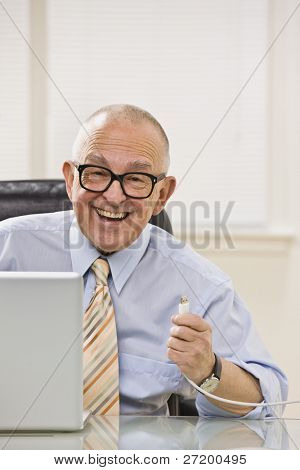 Senior male happy with USB chord in hand, smiling at camera. Vertical